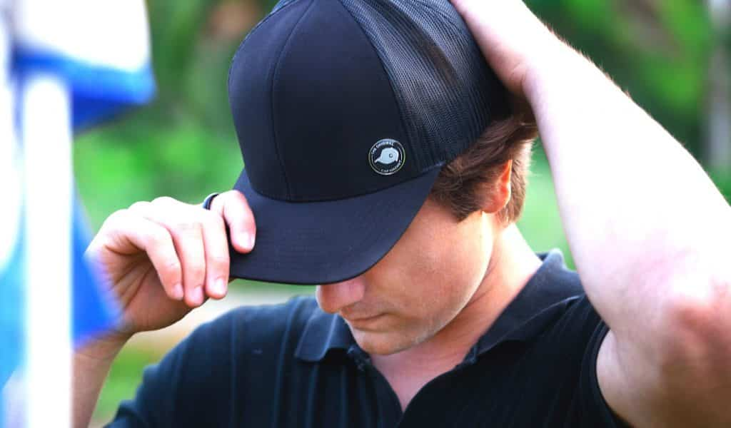 man wearing golf ball marker magnet in lining of a baseball cap on the left hand side