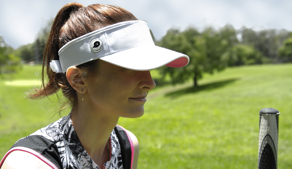 woman with golf ball marker magnet in lining of a white visor and a white ball marker