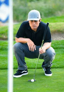 man wearing golf ball marker magnet on left side of ball cap