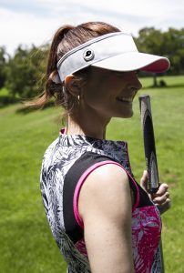 woman wearing golf ball marker magnet in visor with white ball marker