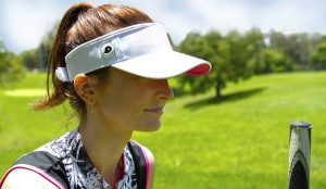 woman with The Original Cap Magnet inside a white visor and a white ball marker